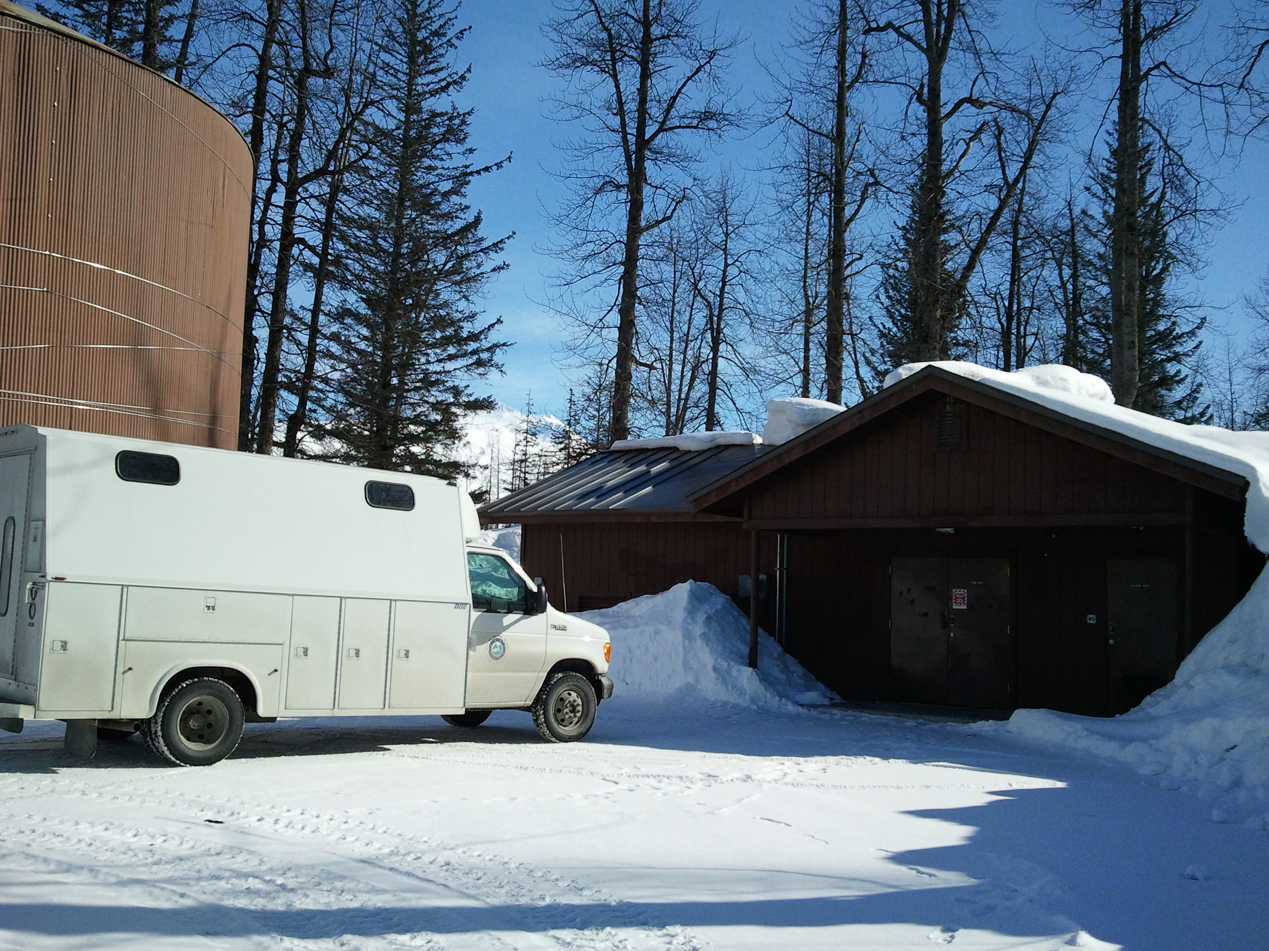 photo of a white van parked in front of a brown building. Winter time